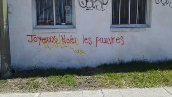 """Graffiti sur un mur blanc """"Joyeux Noël les pauvres"""""""